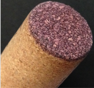Close-up of the end of a micro-agglo cork showing fissures between cork bits where the plastic seems to have dissolved. Photo from a recent purchase by this article's author.